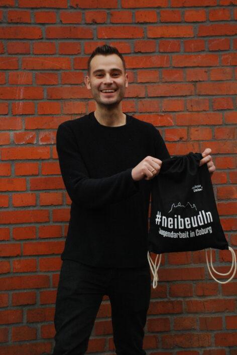 Mark Ritschel präsentiert einen der Turnbeutel, den sich Jugendliche in den Jugendzentren abholen können.