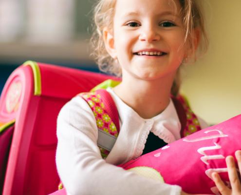 Ein Mädchen mit Schulranzen hält eine rosa Schultüte im Arm